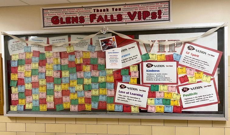 bulletin board display with colorful post-it notes describing VIP students and their accomplishments