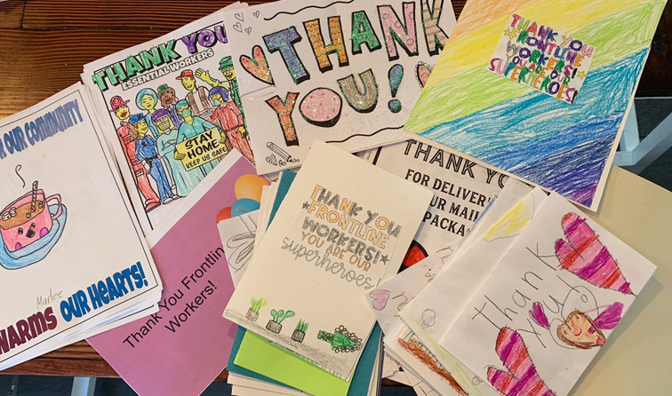 many colorful hand-made cards thanking frontline workers, decorated with crayons and sparkles