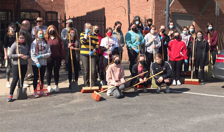 group of students outside with brooms, rakes, shovels