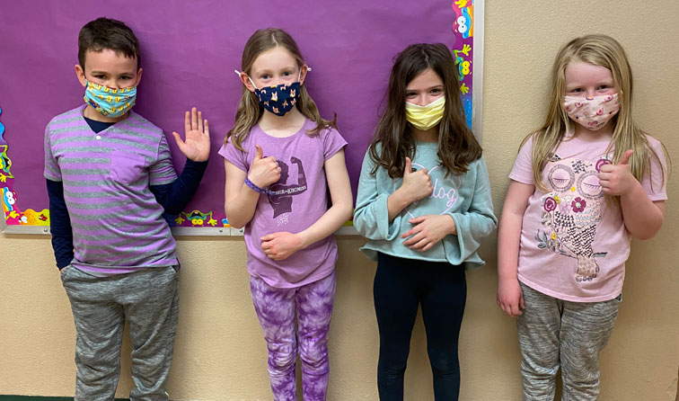 four happy kids in purple wearing face masks