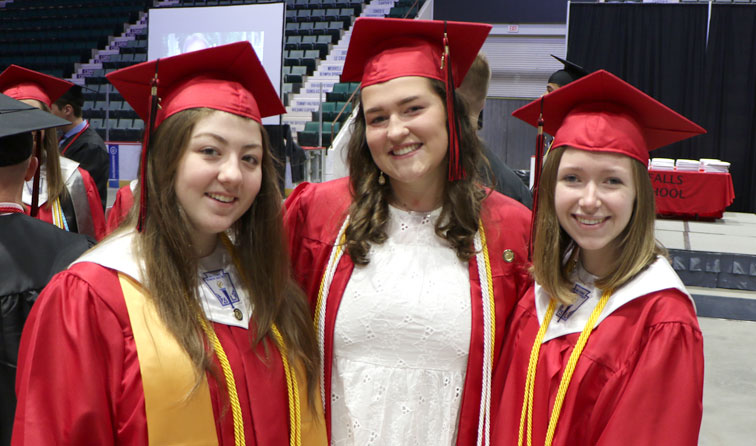 students smiling in their caps and gowns at GFHS graduation ceremony