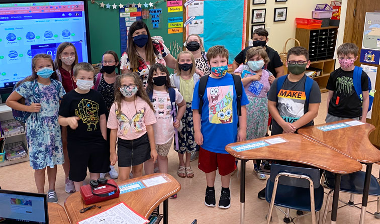 group of students with teacher in classroom, all smiling underneath their face masks