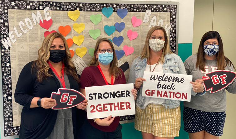 Four teachers in a classroom smiling under their masks and holding welcome back signs