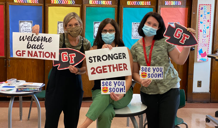 Three teachers in a classroom smiling under their masks and holding welcome back signs