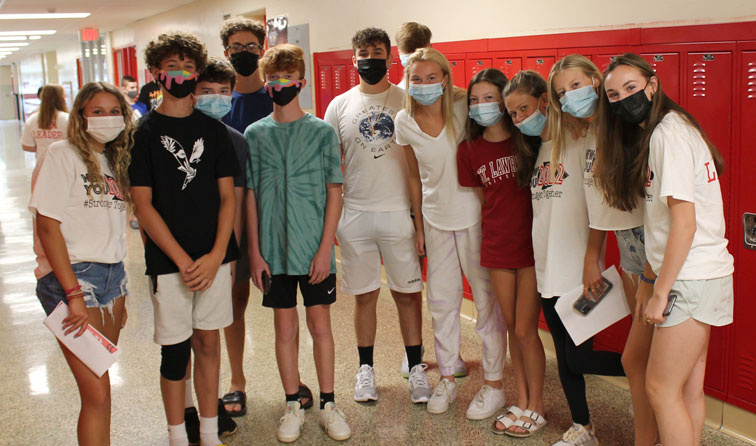 group of high school students standing together in face masks in front of red lockers