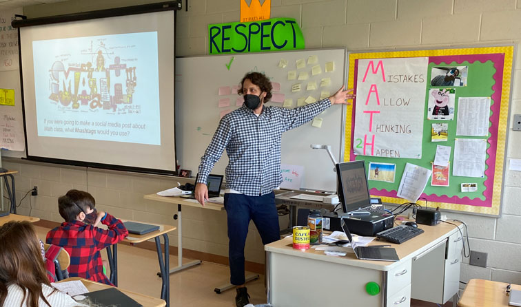 math teacher pointing to sign reading Mistakes Allow Thinking 2 Happen